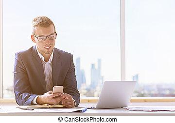 Smiling businessman using smartphone