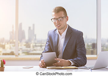 Smiling businessman using tablet