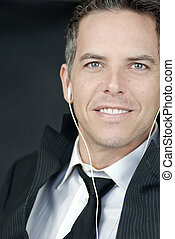 Smiling Businessman Wearing Headphones Looks To Camera