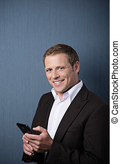 Smiling businessman with a mobile phone