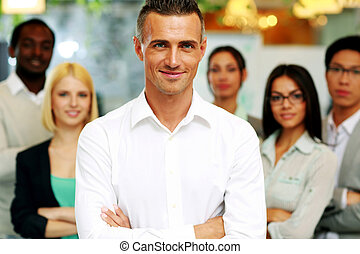 Smiling businessman with arms folded standing in front his colleagues