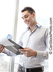 smiling businessman with clipboard in office