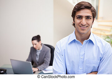 Smiling businessman with colleague on her laptop behind him