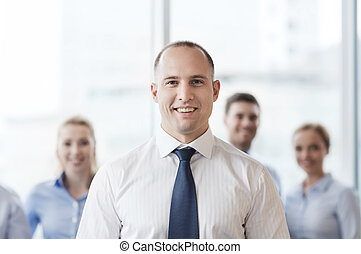 smiling businessman with colleagues in office