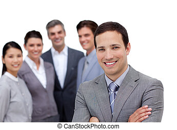 Smiling businessman with folded arms standing with his team