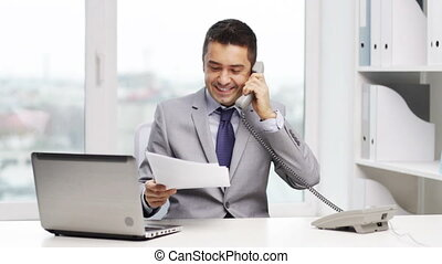 smiling businessman with laptop calling on phone