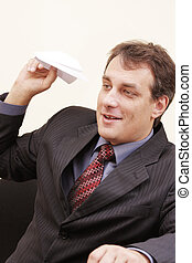 Smiling businessman with paper plane
