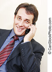 Smiling businessman with phone inclining left