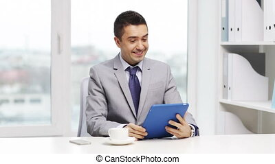 smiling businessman with tablet pc drinking coffee