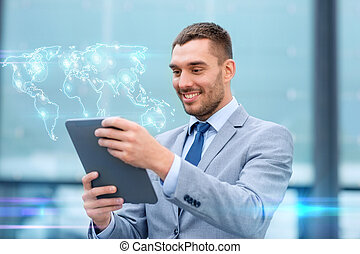smiling businessman with tablet pc outdoors - global...