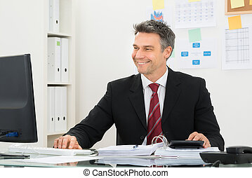 Smiling Businessman Working At Office Desk