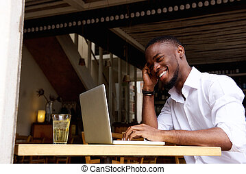 Smiling businessman working on  laptop at cafe