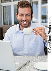 Smiling businessman working with laptop drinking coffee