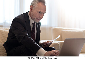 Smiling businessman working with papers and looking at the laptop