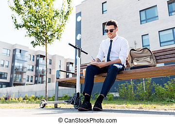 smiling businessman writing to notebook in city