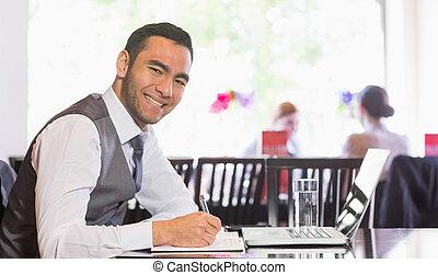Smiling businessman writing while looking at camera