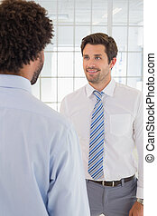 Smiling businessmen looking at each other in office