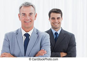 Smiling businessmen posing looking at camera