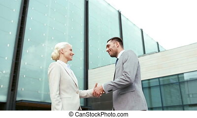smiling businessmen shaking hands on street - business,...