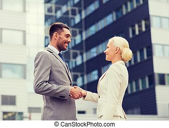 smiling businessmen standing over office building -...
