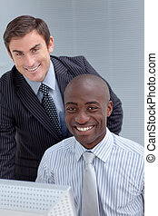 Smiling businessmen using a computer together