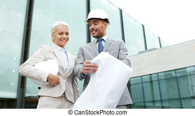 smiling businessmen with blueprint and helmets