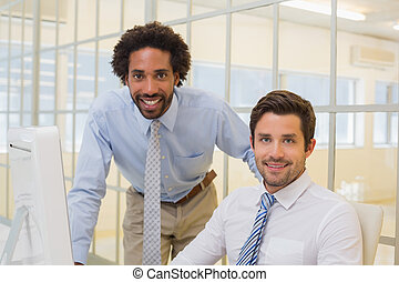 Smiling businessmen with computer in office