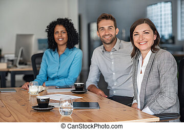 Smiling businesspeople sitting together at an office table