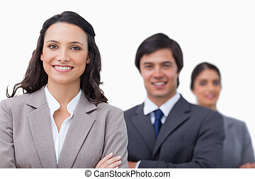 Smiling businesspeople standing with arms folded