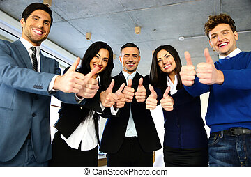 Smiling businesspeople standing with thumbs up in office