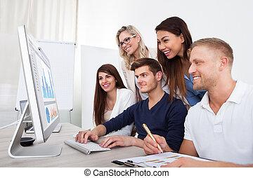 Smiling Businesspeople Using Desktop PC