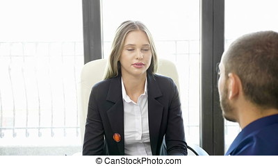 Smiling Businesswoman and businessman talking in the office