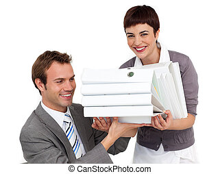 Smiling Businesswoman bringing a stack of folders to her manager in the office
