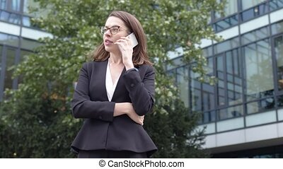 Smiling businesswoman browsing smartphone near office building