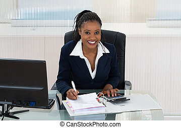 Smiling Businesswoman Calculating Bills