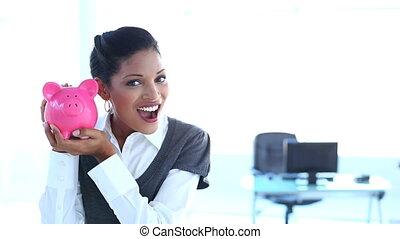 Smiling businesswoman checking pigg