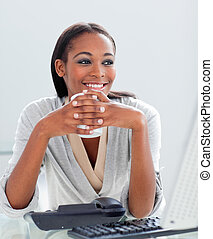 Smiling businesswoman drinking a coffee at her desk