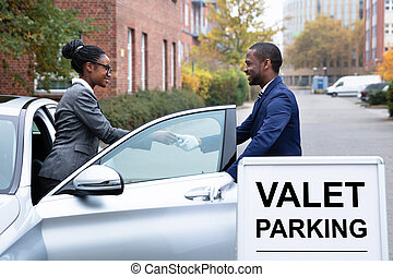 Businesswoman Giving Car Key To Male Valet - Smiling...