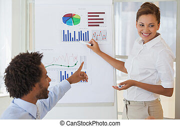 Smiling businesswoman giving presentation to colleague