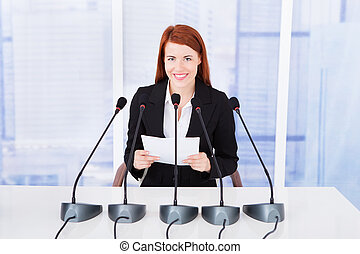 Smiling Businesswoman Giving Speech At Conference