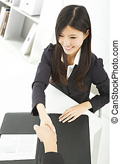 smiling businesswoman handshaking with businessman in the office