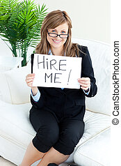 "Smiling businesswoman holding a paper with the tite""Hire Me!\"""