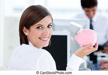 Smiling businesswoman holding a pig