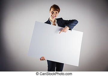Smiling businesswoman holding and pointing to poster on grey...