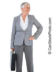 Smiling businesswoman holding briefcase and putting her hand on hip on white background