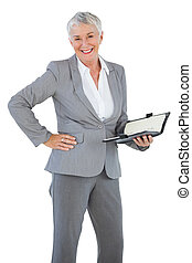Smiling businesswoman holding diary with her hand on hip