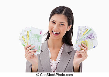 Smiling businesswoman holding money in her hands