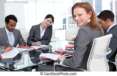 Smiling businesswoman in a meeting with her team