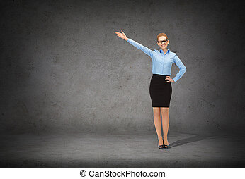smiling businesswoman in glasses pointing her hand