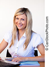 Smiling businesswoman in office using a laptop